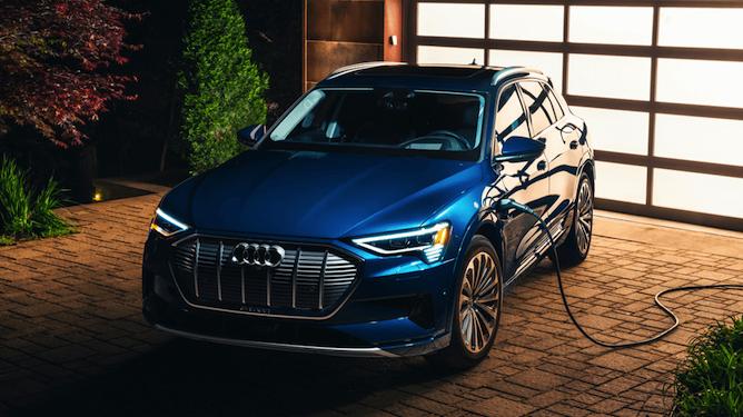 Blue Audi Sedan plugged in in the driveway at night.