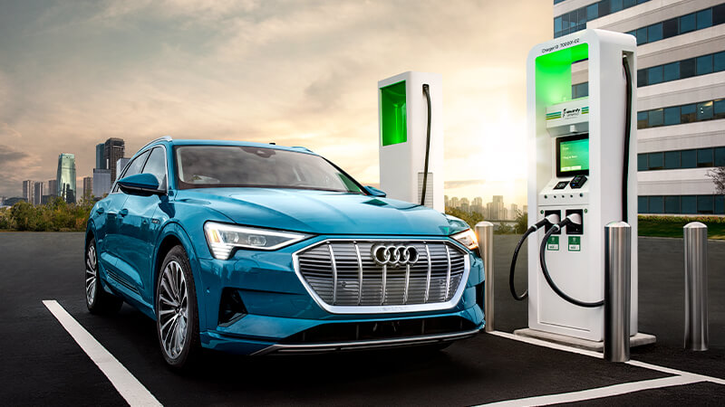 A blue Audi SUV at a charging station, charging.