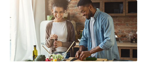 Couple in a kitchen cooking with vegetables.