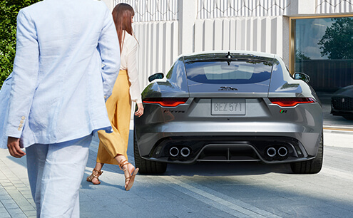 Jaguar F-TYPE on road with two people walking behind